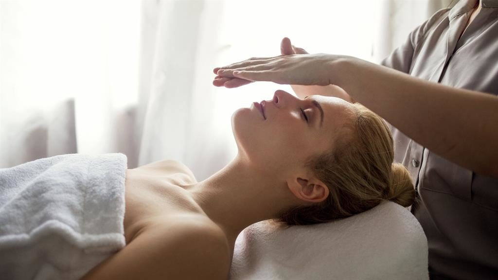 Calming palming: A reiki therapist channels energy and Martha's healthy look after treatment (below)