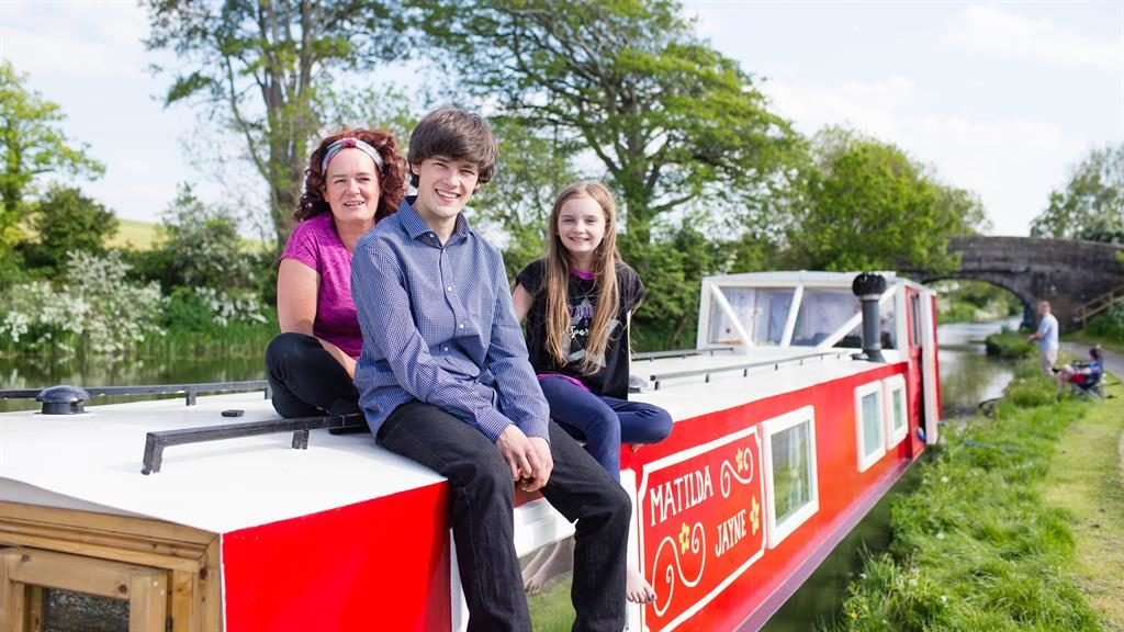 Oh buoy: Billy with mum Jayne and sister Matilda on the canal boat he renovated in just eight weeks PICTURES: CATERS