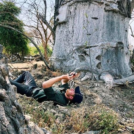 Majestic: Harry takes a picture of the two trees while lying on his back in Liwonde National Park. He then posted both shots on Instagram