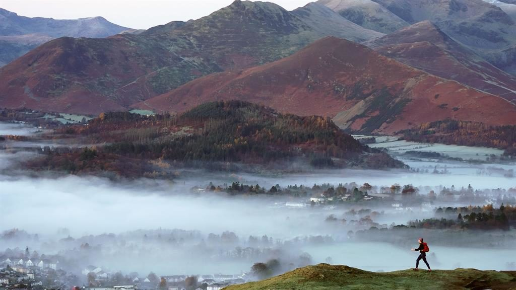 In the clouds: A walker in the mist over Keswick in the Lake District PICTURE: PA