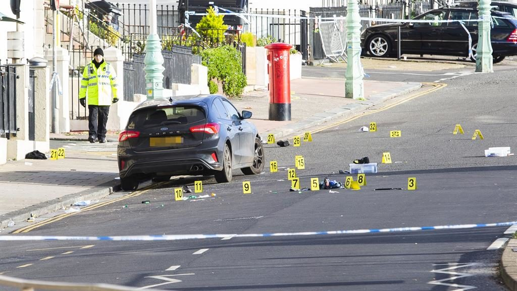 Coned off: Road on Brighton seafront is closed as forensic officer (below) looks under car for clues PICTURES: LNP