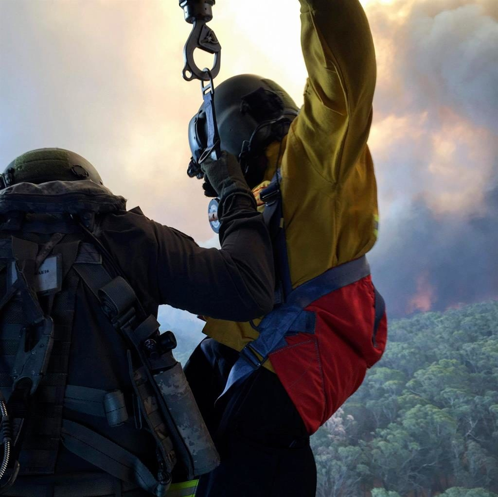 So brave: Crewman is winched down into the inferno in search of people trapped by the bush fires PICTURES: POIS HELEN FRANK/COMMONWEALTH