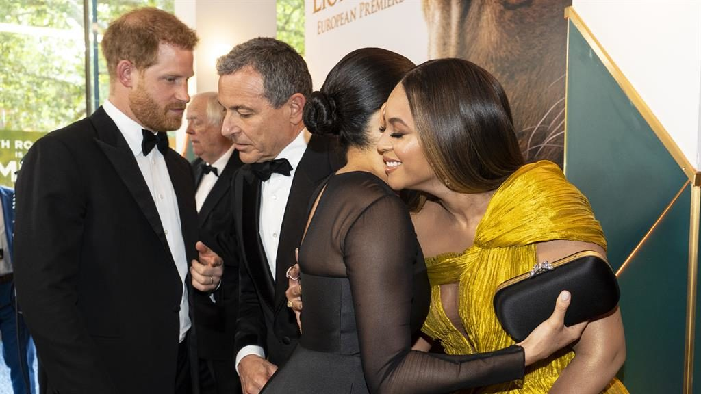 Making a point: Harry talks to Disney boss Bob Iger as Meghan and Beyoncé hug PICTURE: GETTY