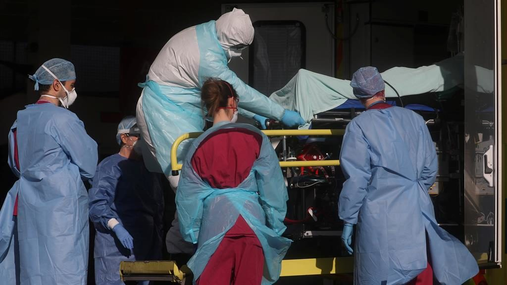 Life-savers: Medical staff in protective gear take a patient off an ambulance at St Thomas' hospital, London PICTURE: REUTERS