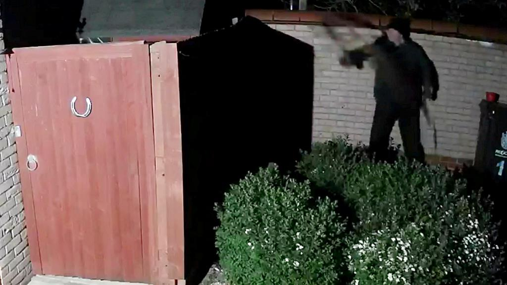 Loodunnit: The man is seen throwing an unknown substance at the Purchases' shed PICTURE: SWNS