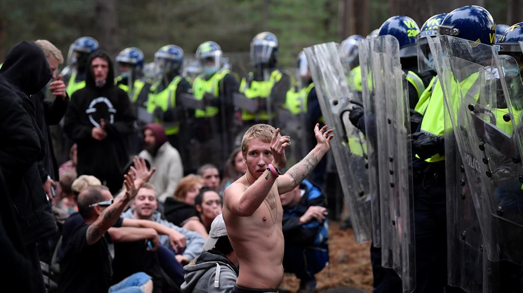 Hands up: A raver faces a line of riot police in Norfolk's Thetford Forest on Sunday night PICTURE: TOBY MELVILLE/REUTERS
