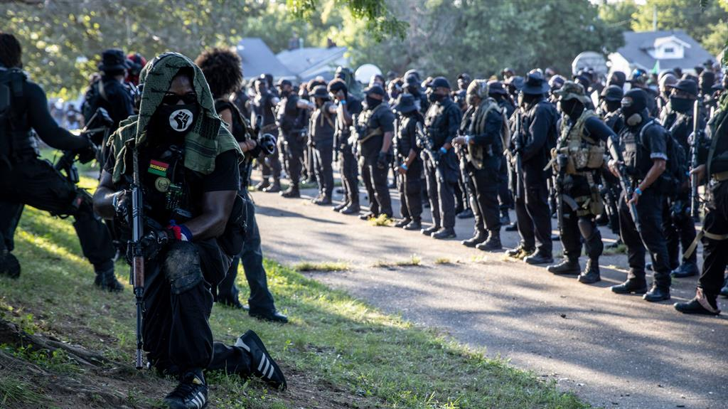 Showdown: Members of a black militia and (below) tense stand-off PICTURES: REX