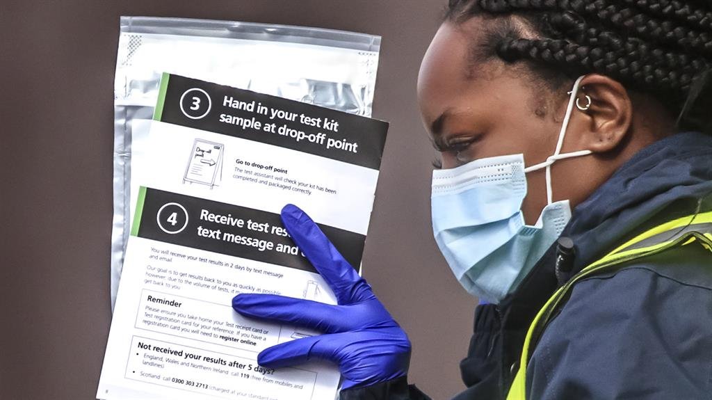 Infections: Staff hand out self-test kits at a coronavirus testing centre in Bolton PICTURES: PA