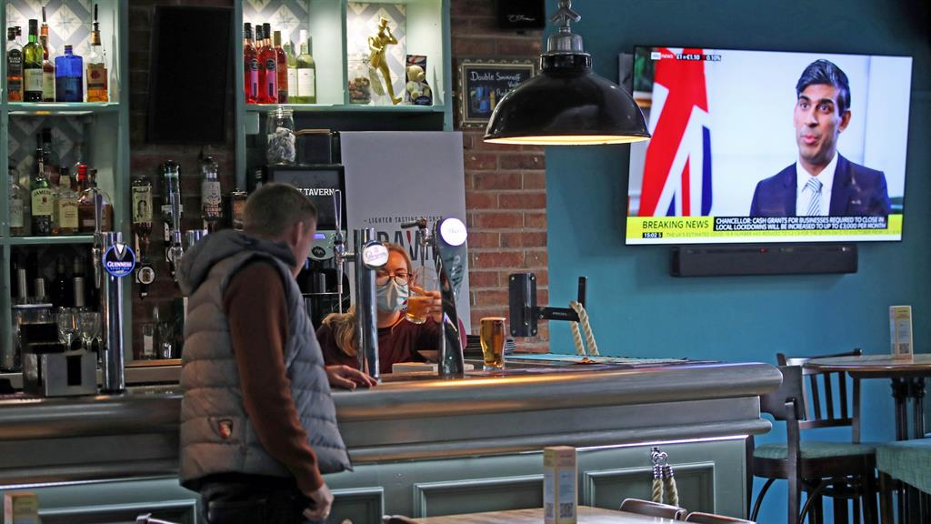 Topped up: An employee pulls a pint at a bar in Manchester, as Rishi Sunak makes today's announcement PICTURE: PA
