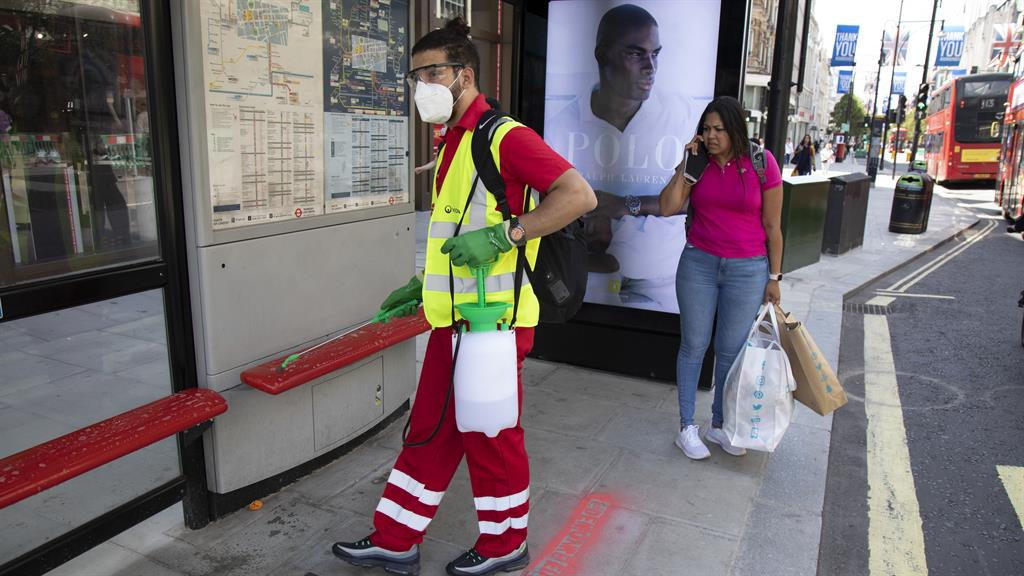 Taking no chances: A TfL worker makes sure a bus stop is germ-free PICTURE: GETTY