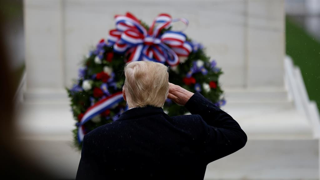 About time: Mr Trump gives a salute and (below) looking sombre at the Veterans Day ceremony PICTURES: REUTERS/REX/GETTY