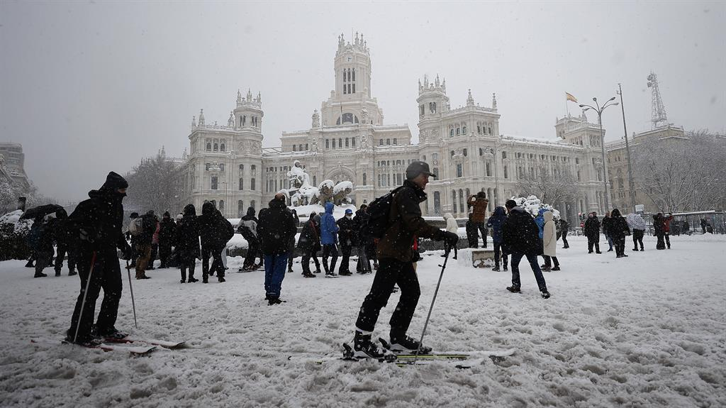 Chilling out: People walk and ski at Madrid's Plaza de Cibeles and (below) cars buried by snow PICTURES:GETTY/REX