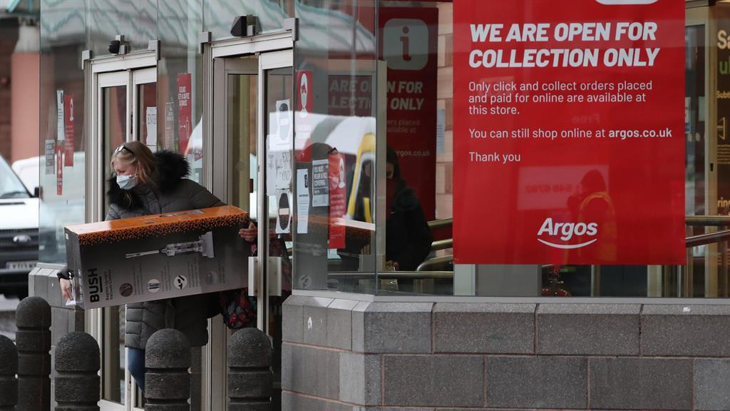 Rule changes: A woman collects a parcel from an Argos store in Glasgow. Click-and-collect services for non-essentials will end in Scotland from Saturday PICTURE: PA